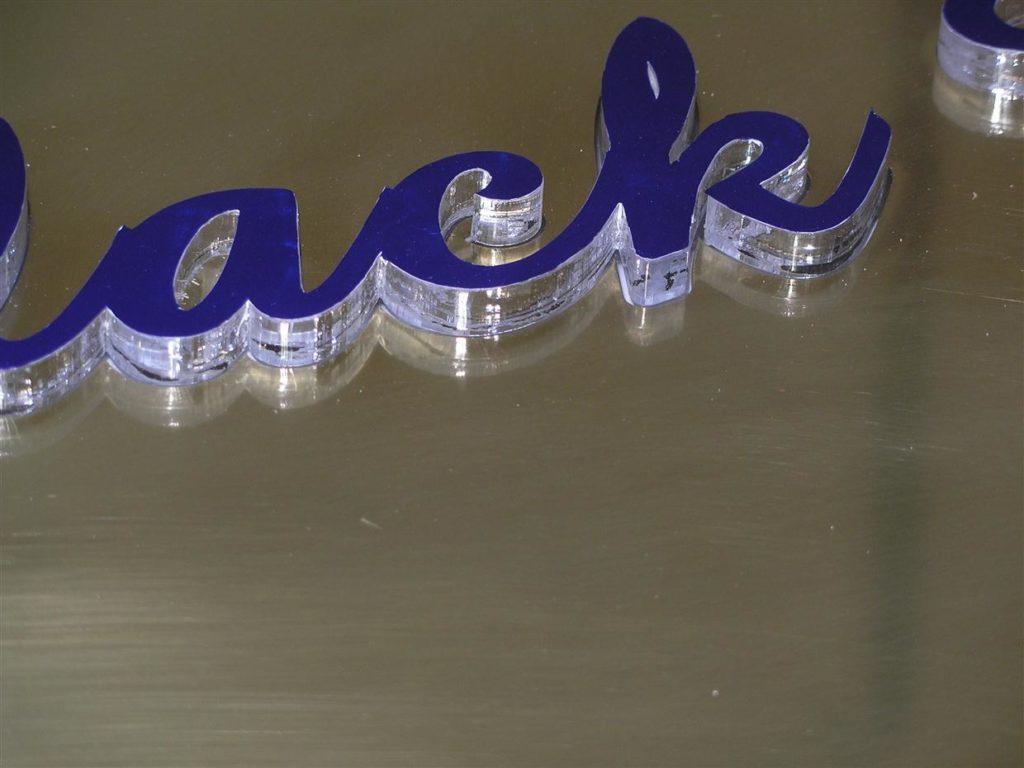 Debel pleksi napis- montiran na medenino. Sveti samo stranica