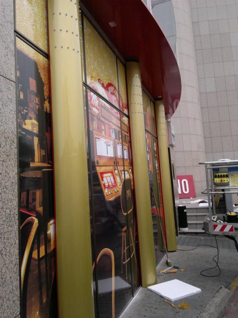 Pročelje, vhod casino Lev. Lakirani svetlobni stebri. Polepitev stekel.